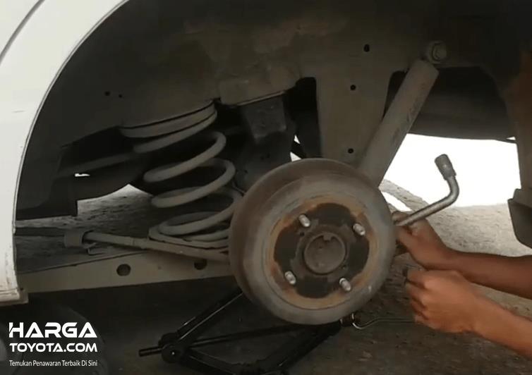 Gambar ini menunjukkan bagian roda mobil Toyota Avanza dan terdapat shockbreake