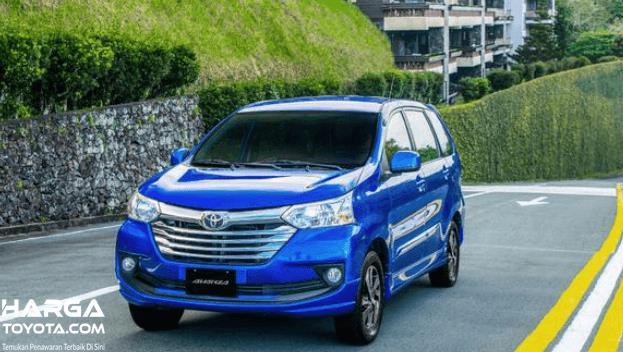 Gambar ini menunjukkan mobil Toyota Avanza warna biru melaju di jalanan
