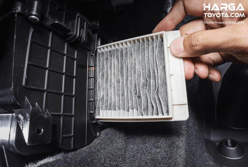Ga,bar ini menunjukkan sebuah tangan menarik filter udara pada mobil