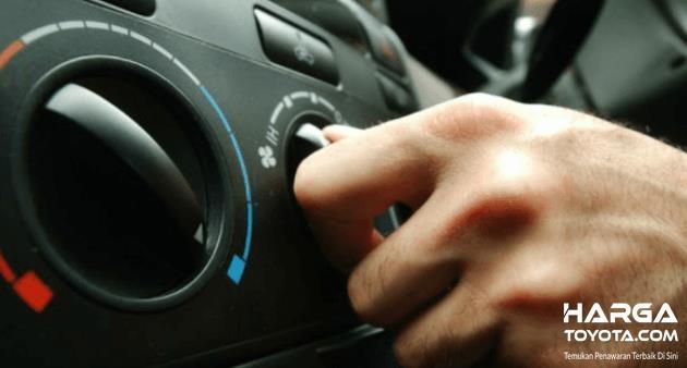 Gambar ini menunjukkan sebuah tangan memegang panel pengatur AC Mobil