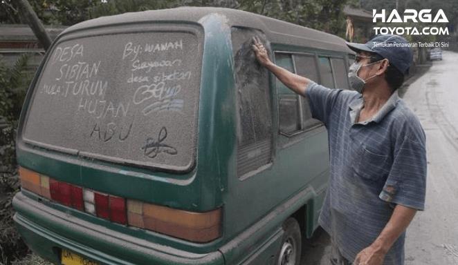 Gambar ini menunjukkan seorang pria berdiri di samping mobil yang tertutup dengan abu vulkanik