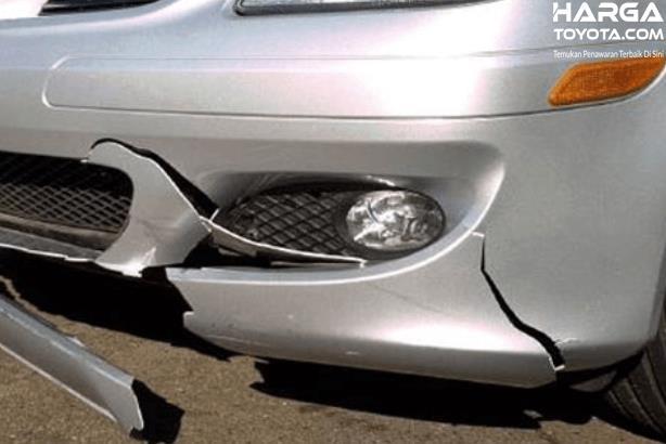 Gambar ini menunjukkan bumper mobil warna silver dalam kondisi pecah
