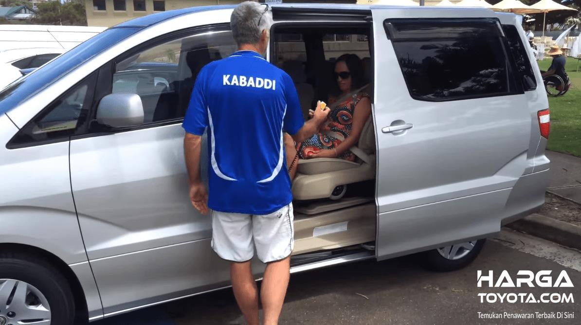 Gambar ini menunjukkan Toyota Alphard dan terdapat 2 orang satu pria dan satu wanita di dalam mobil