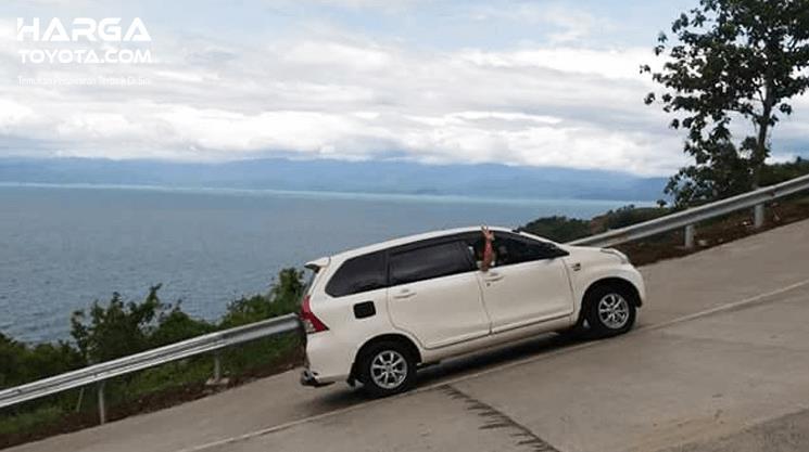 Gambar ini menunjukkan mobil warna putih sedang melintasi tanjakan