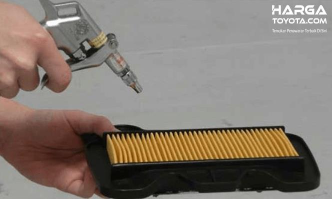 Gambar ini menunjukkan  sebuah tangan  memegang alat penyemprot angin diarahkan ke filter udara