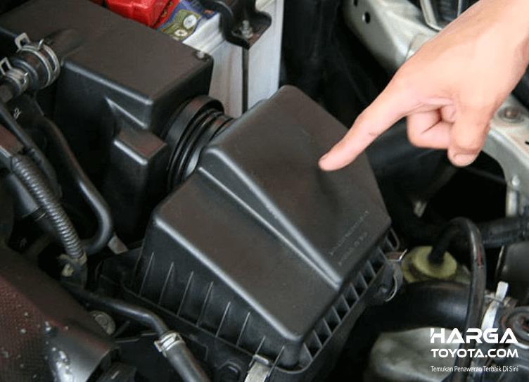 Gambar ini menunjuk sebuah tangan menunjuk rumah filter pada mobil