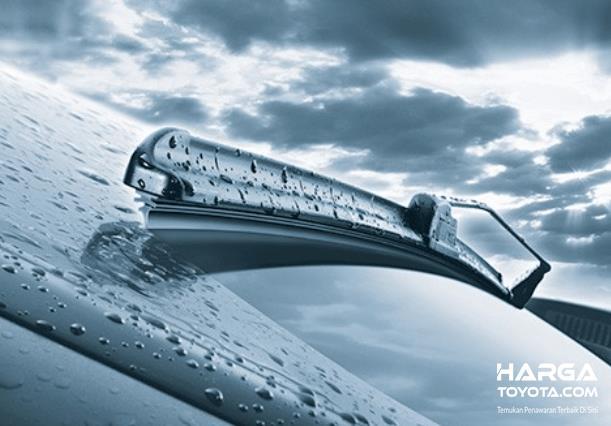 Gambar ini menunjukkan wiper mobil sedang mengusap kaca mobil basah