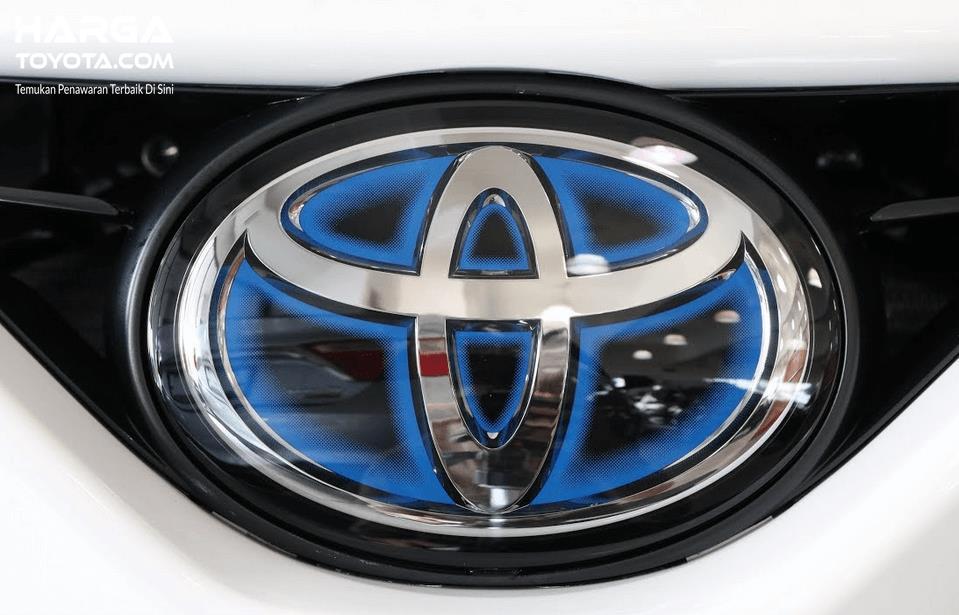Gambar ini menunjukkan logo mobil Toyota dengan aksen warna krom, hitam dan biru