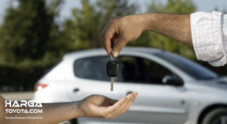 Gambar ini menunjukkan 2 buah tangan lagi menyerahkan kunci