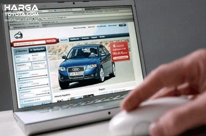 Gambar ini menunjukkan sebuah tangan menekan tombol pada laptop yang terdapat gambar mobil