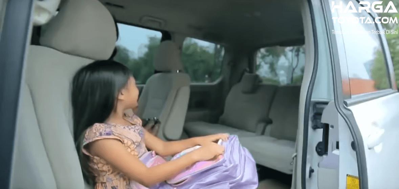 Gambar ini menunjukkan seorang anak perempuan sedang duduk di dalam kabin Toyota NAV1