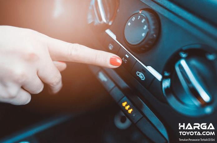 Gambar ini menunjukkan sebuah tangan menekan tombol untuk menyalakan AC mobil