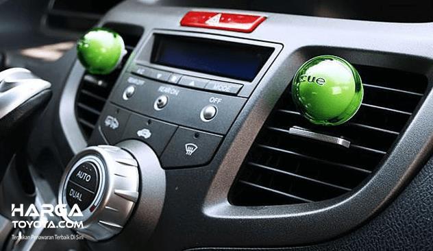 Gambar ini menunjukkan head unit pada dashboard mobil dan terdapt 2 parfum mobil