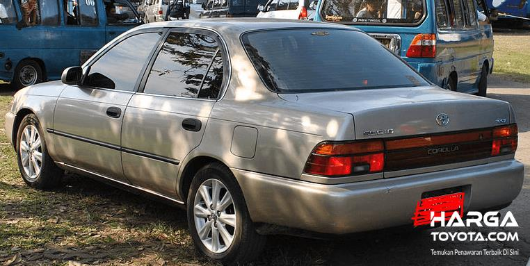 Gambar ini menunjukkan mobil Toyota Great Corolla tampak belakang dan di depannya ada mobil warna biru