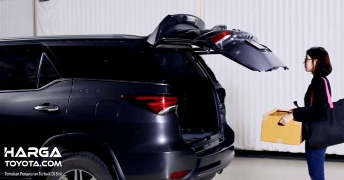 Gambar ini menunjukkan sebuah mobil dengan pintu belakang terbuka dan terdapat seorang wanita sedang berdiri