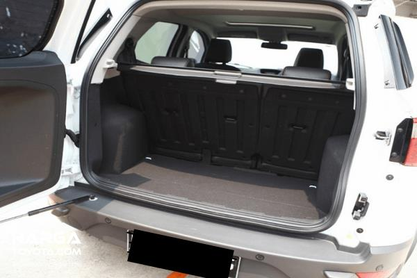 Gambar ini menunjukkan sebuah mobil warna putih dengan pintu bagasi terbuka