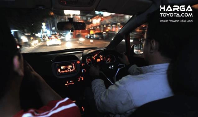 Gambar  ini menunjukkan 2 orang di dalam mobil yang satu sedang mengemudi