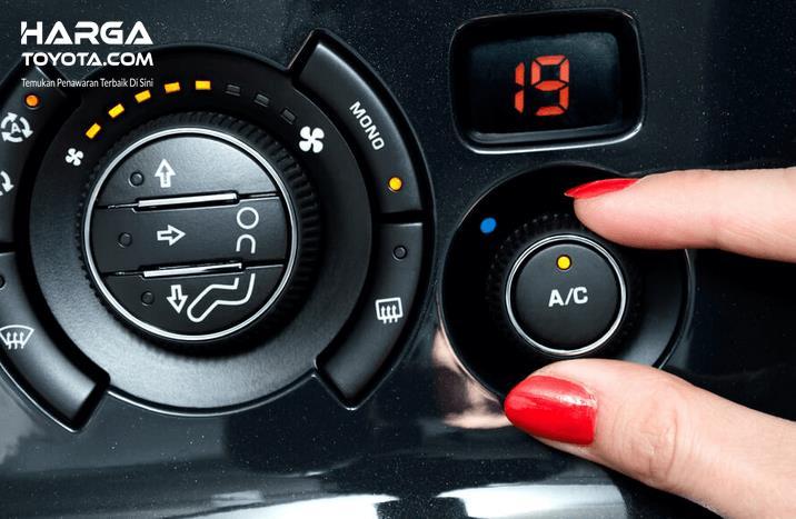Gambar ini menunjukkan sebuah tangan memutar knob untuk mengatur temperatur AC