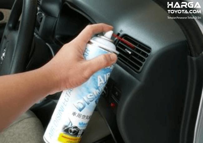 Gambar ini menunjukkan sebuah tangan memegang cairan khusus disemprotkan pada kisi-kisi AC mobil