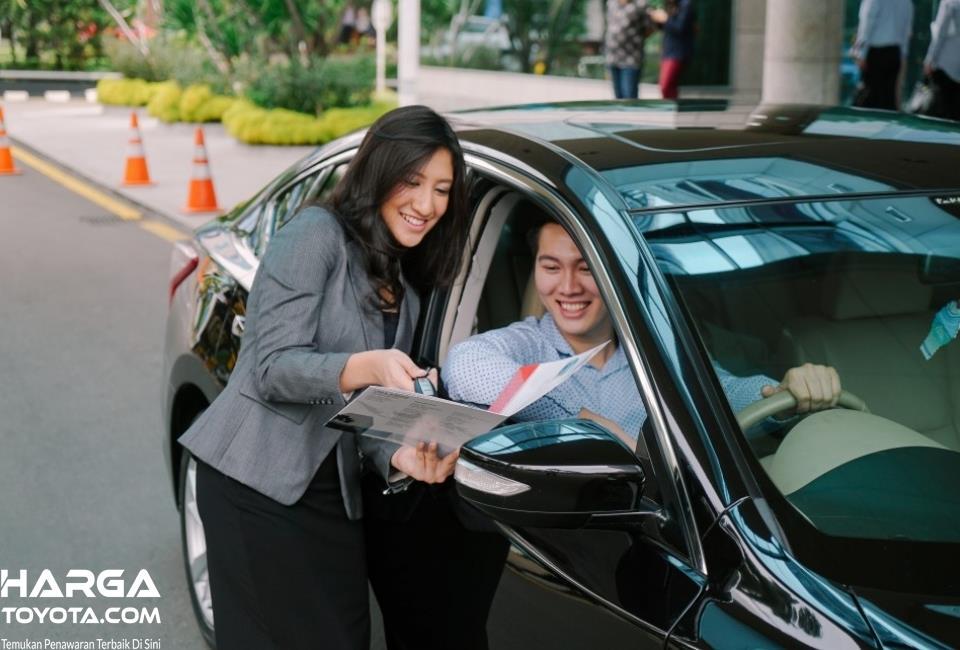 Foto seorang sales mobil bekas memberikan penjelasan seputar mobil yang ditawarkan kepada calon konsumen