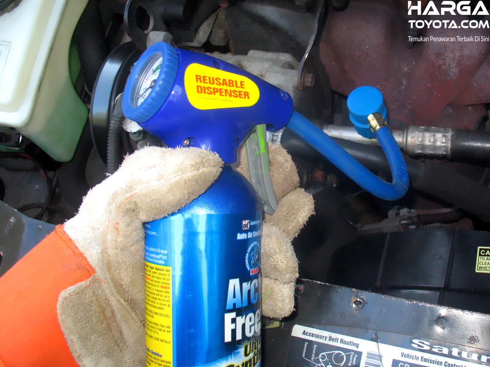 teknisi yang sedang mengisi ulang freon AC pada mobil