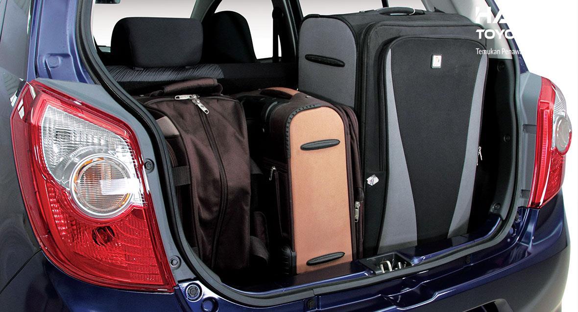 beberapa koper pada bagasi mobil Toyota berwarna biru