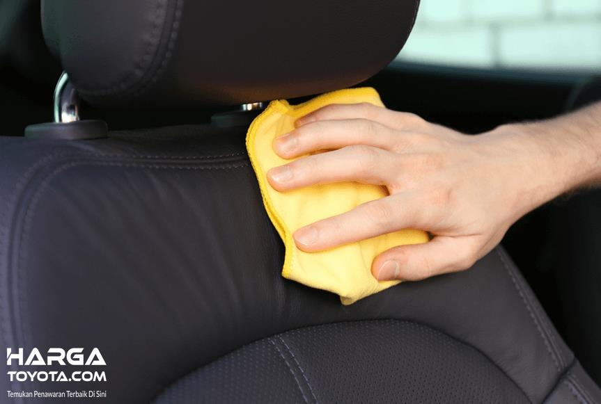 Gambar ini menunjukkan sebuah tangan memegang kain ditempelkan pada jok mobil