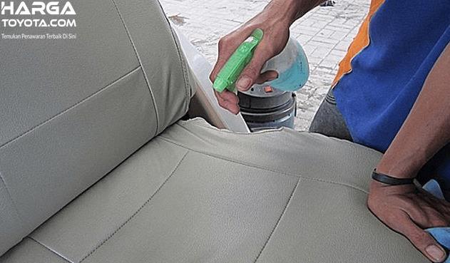 Gambar ini menunjukkan seorang pria memegang cairan disemprotkan pada jok mobil