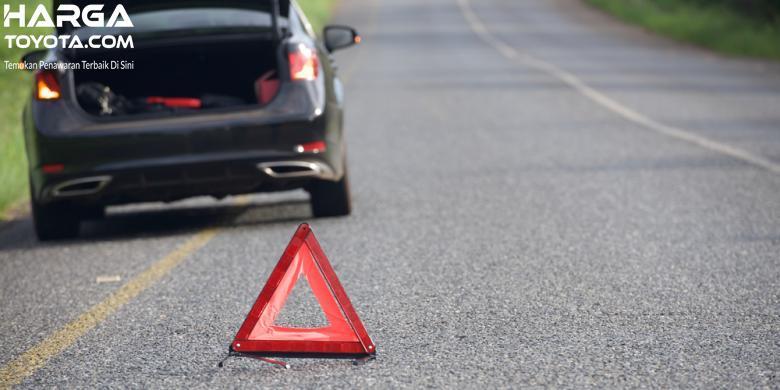mobil berwarna hitam dengan segitiga pengaman berwarna merah