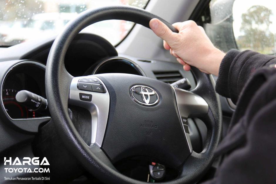 pengemudi yang sedang memegang kemudi berwarna hitam
