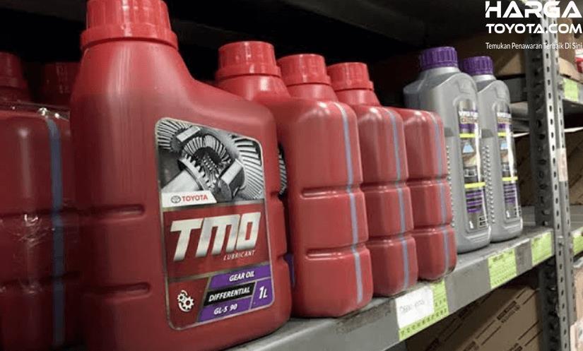Gambar ini menunjukkan oli TMO dengan botol warna merah dan silver