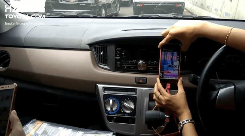 Gambar ini menunjukkan sebuah tangan memegang ponsel di kabin Toyota Calya