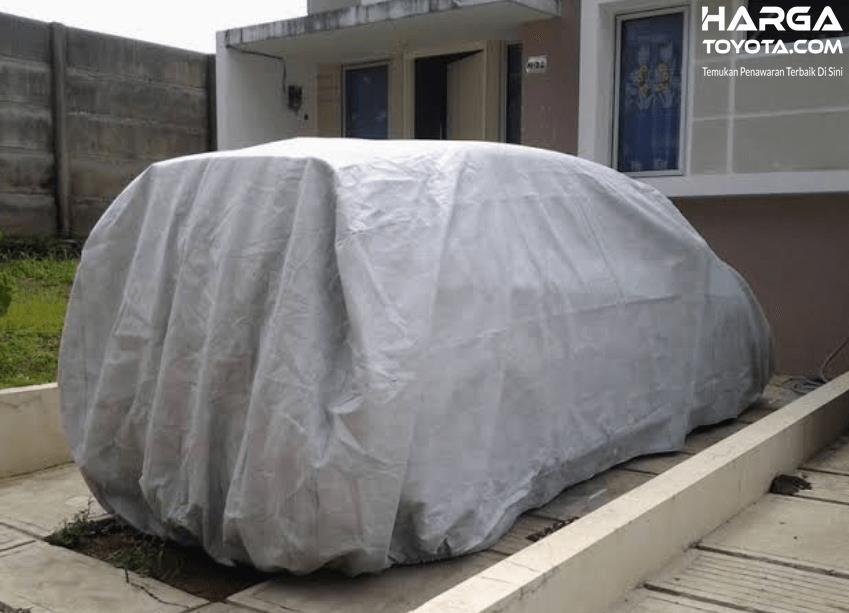 Gambar ini menunjukkan sebuah mobil yang tertutup cover warna silver