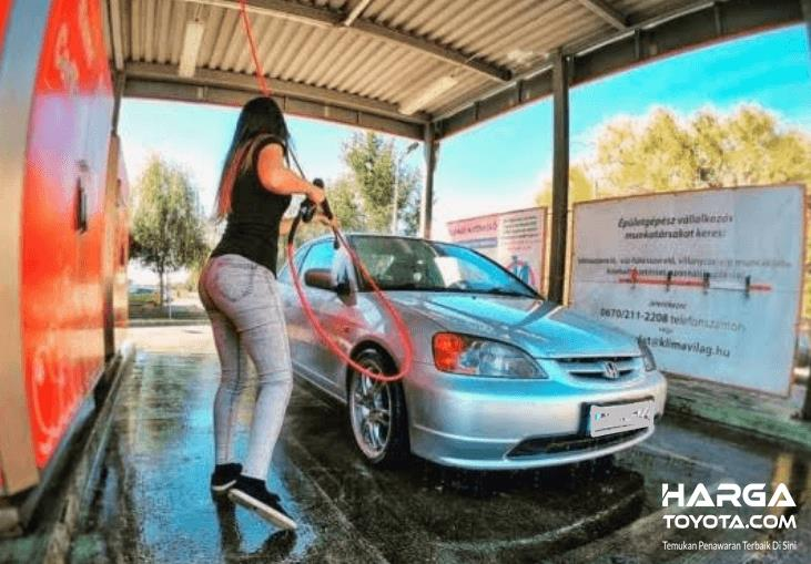 Gambar ini menunjukkan seorang wanita sedang mencuci kendaraan