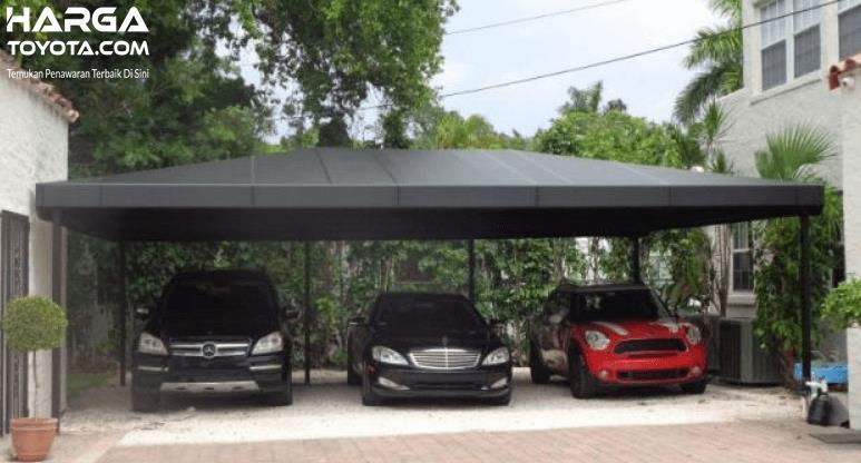 Gambar ini menunjukkan 3 mobil terparkir rapi di bawah atap