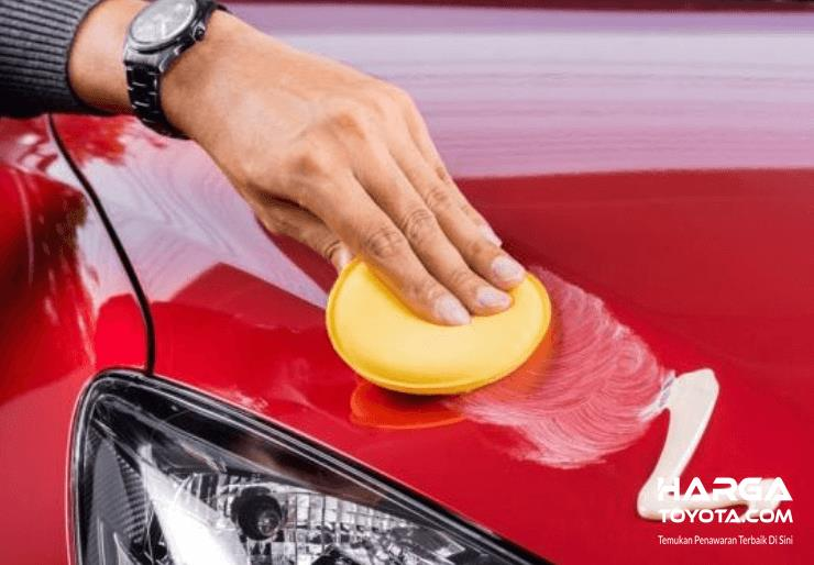 Gambar ini menunjukkan  sebuah tangan memegang sesuatu untuk waxing bodi mobil