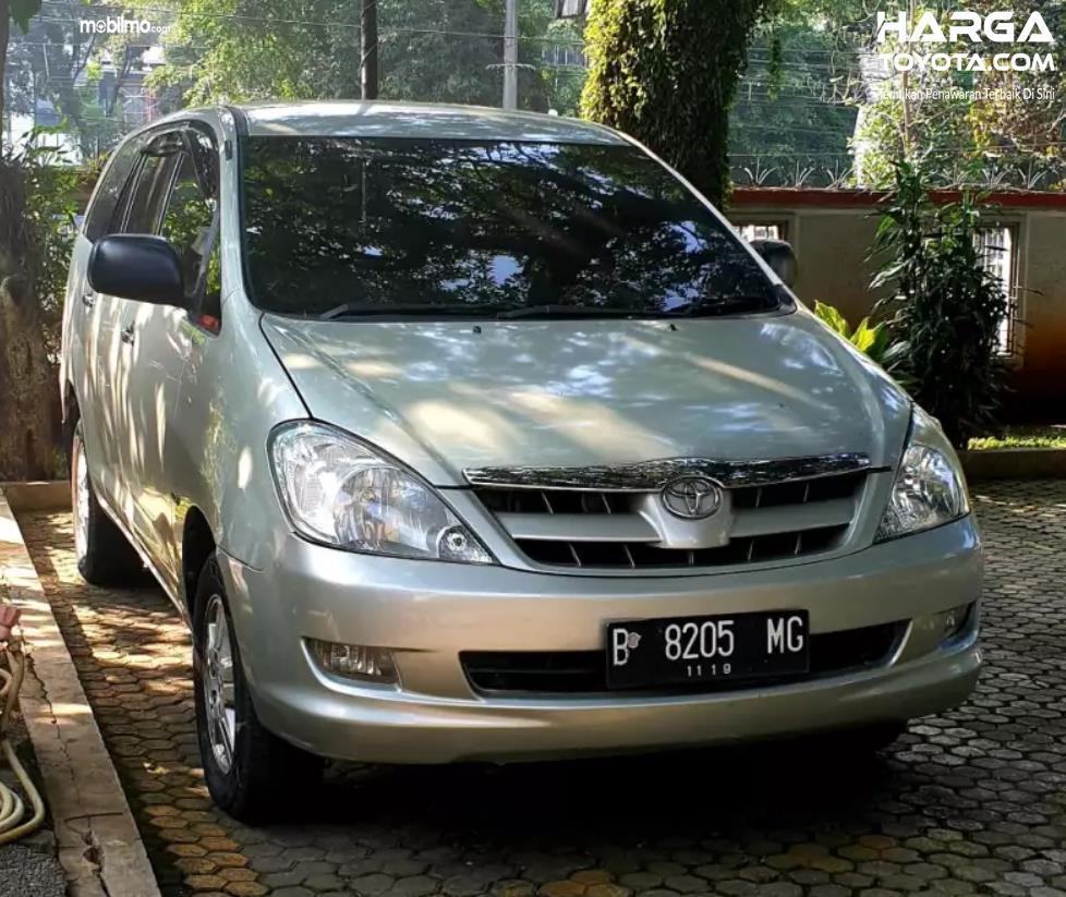 mobil Innova berwarna putih di bawah pohon