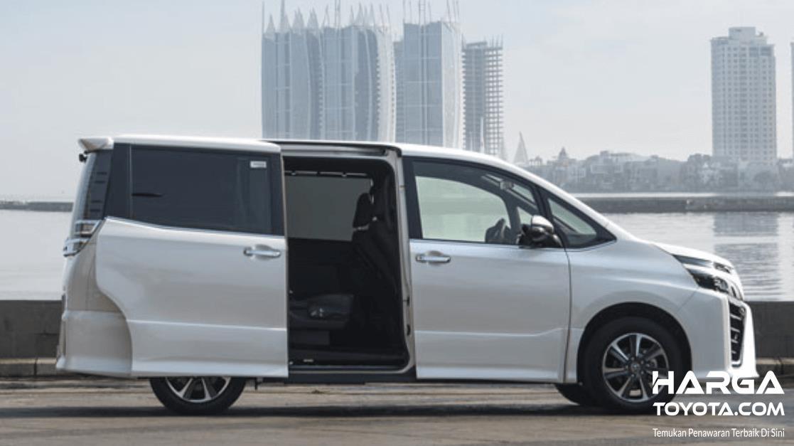 Gambar ini menunjukkan Toyota Voxy warna putih dengan pintu geser terbuka