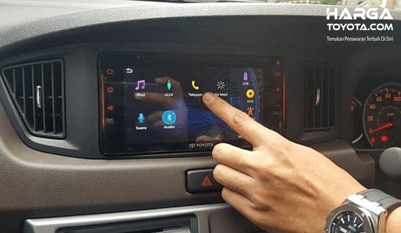Gambar ini menunjukkan sebuah jari menekan gamba telepone pada layar