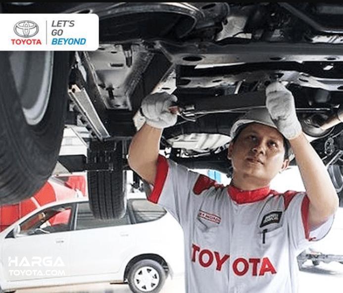 Gambar ini menunjukkan mekanik Toyota sedang memperbaiki bawah mobil
