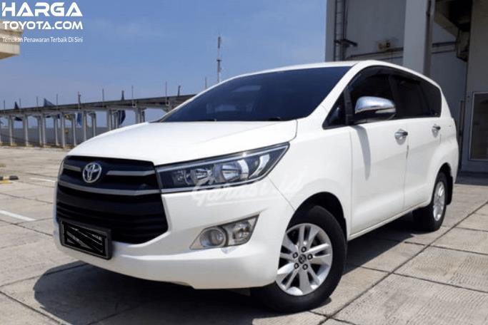 Gambar ini menunjukkan mobil Toyota Kijang Innova putih tampak depan