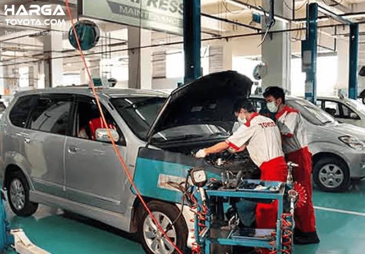 Gambar ini menunjukkan mekanik sedang melihat mesin mobil kendaraan di bengkel resmi