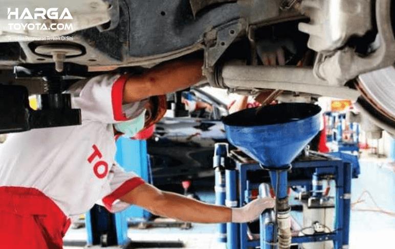 Gambar ini menunjukkan seorang mekanik bengkel resmi Toyota sedang merawat mesin mobil