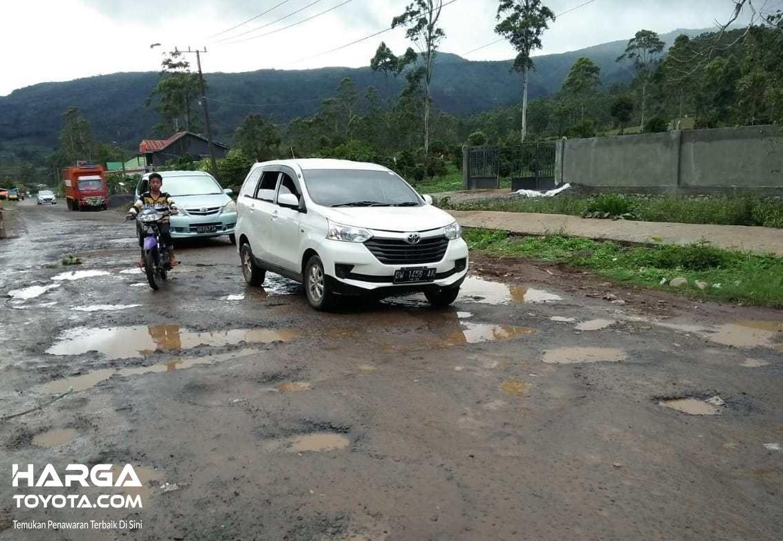 Foto kendaraan melewati jalanan berlobang dengan pelan
