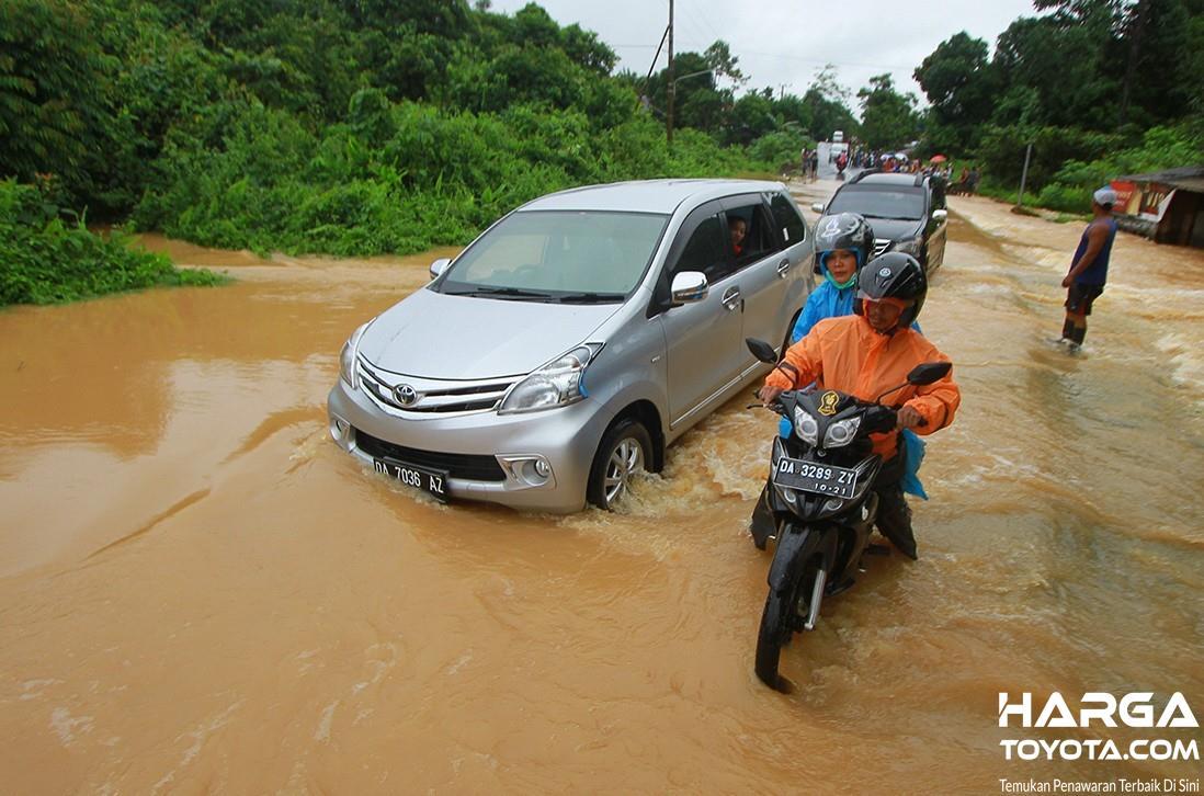 Foto mobil dan sepeda motor menerobos banjir yang melanda hingga jalan raya