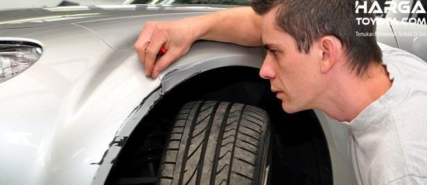Mengecek eksterior mobil khususnya pada kondisi baret hingga karat pada sisi bawah mobil