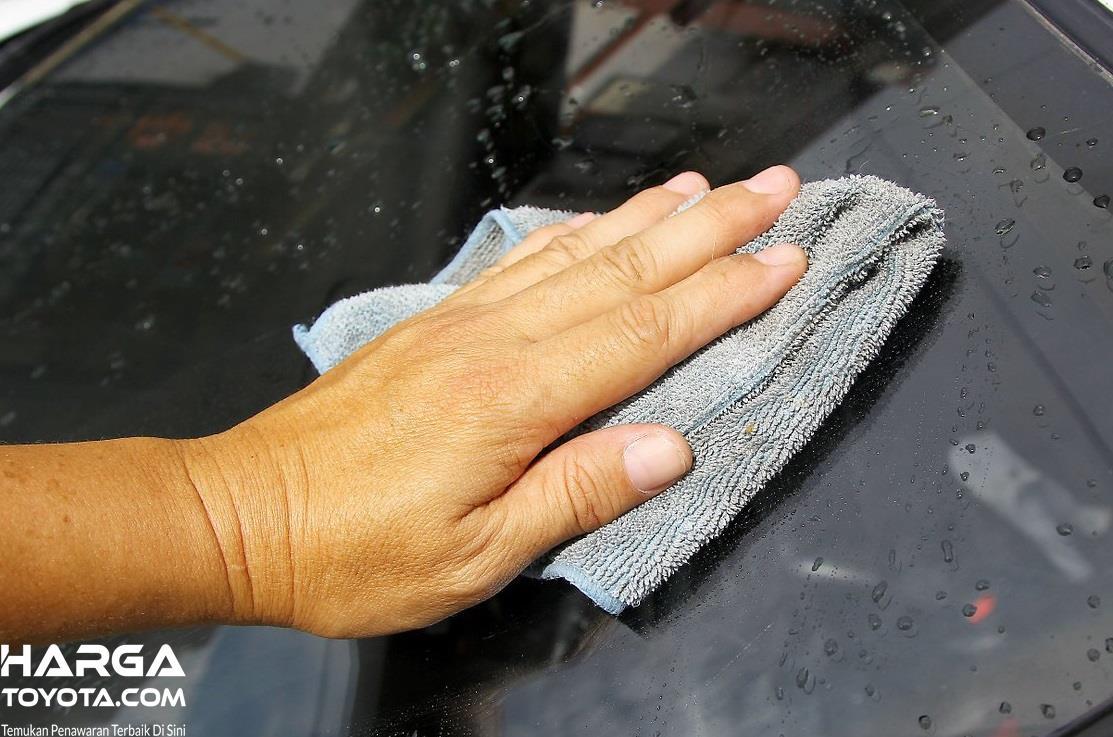 tangan yang sedang membersihkan jendela mobil berwarna hitam