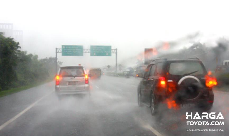 Gambar ini menunjukkan beberapa mobil melaju di musim hujan dengan lampu belakang menyala