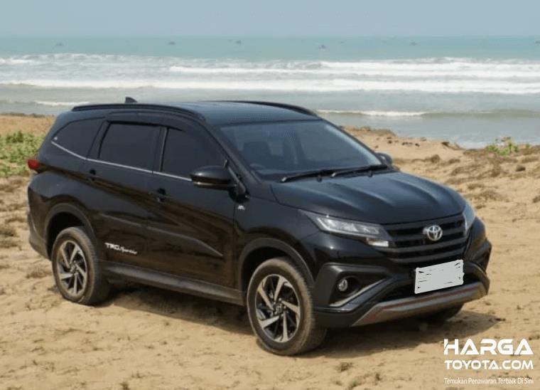 Gambar ini menunjukkan Toyota New Rush Hitam berada di dekat pantai