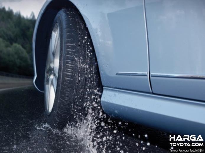 Gambar ini menunjukkan ban mobil sedang melintasi jalan ang berair